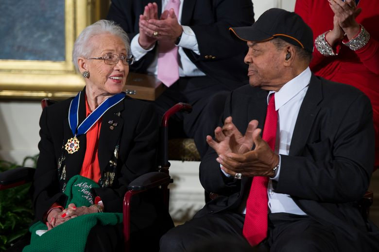 """FILE – In a Nov. 24, 2015 file photo, Willie Mays, right, applauds NASA mathematician Katherine Johnson, after she received the Presidential Medal of Freedom from President Barack Obama during a ceremony in the East Room of the White House. The street outside of NASA's Washington headquarters has been renamed """"Hidden Figures Way"""" to honor the African American women who served as """"human computers"""" in the effort to send humans to the moon. News outlets report dignitaries gathered Wednesday, June 12, 2019 in Washington, D.C., to unveil the new street sign.  (AP Photo/Evan Vucci, File)"""
