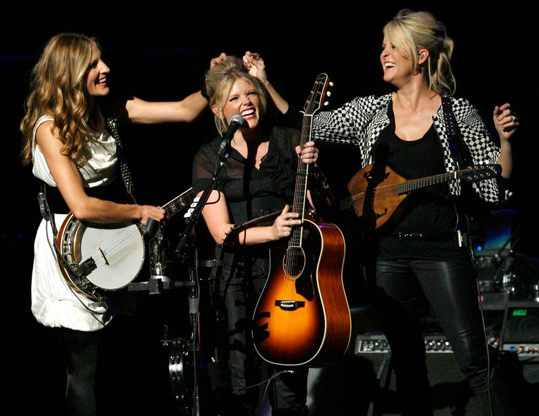 FILE – In this Oct. 18, 2007 file photo, Emily Robison, left, and Martie Maguire, right, adjust Natalie Maines' hair as the Dixie Chicks perform at the new Nokia Theatre in Los Angeles.  The award-winning group took to Instagram on Tuesday, June 25, 2019  to tease a new album. It would be their first in 13 years. (AP Photo/Gus Ruelas, file)
