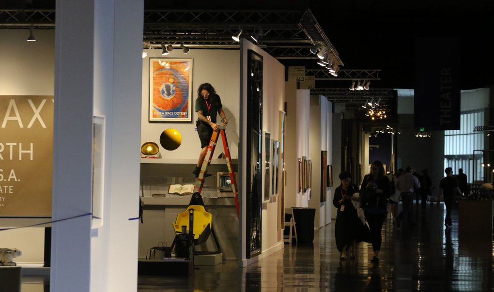 Adjustments are made at an exhibitor's space at the 2018 Seattle Art Fair at CenturyLink Event Center. Last year, about 22,500 people attended, and about the same number is expected this year. (Alan Berner / The Seattle Times, 2018)