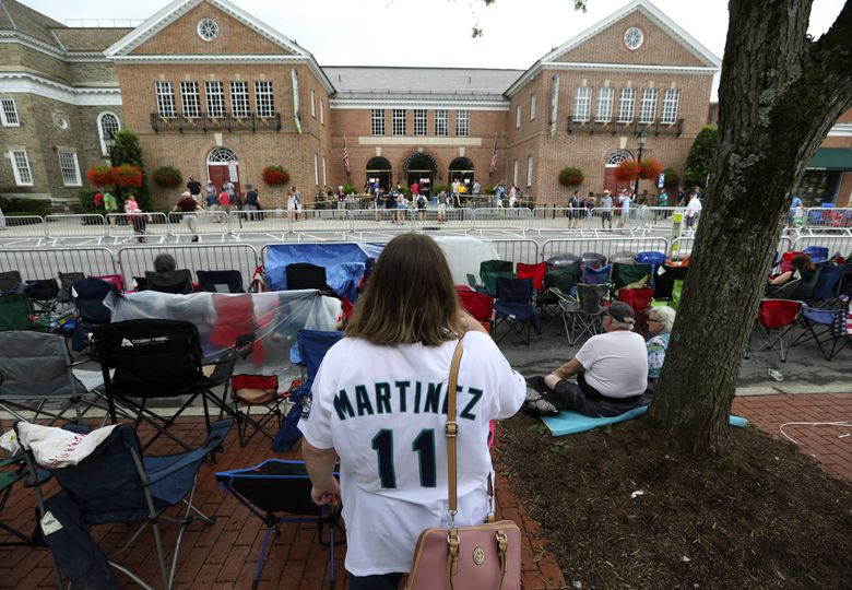 """Tammie Carr of Sunnyside, Wash., looks out across Main Street at the National Baseball Hall of Fame, and said she's looking forward to inductee Edgar Martinez finally going in, Saturday, July 20, 2019 in Cooperstown, NY. """"I said I wouldn't go to the Hall of Fame until Edgar got in."""" (Ken Lambert / The Seattle Times)"""