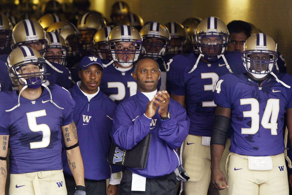 Tyrone Willingham leads the Huskies out of the tunnel in uniforms from an era of Husky football many fans would like to forget. (Dean Rutz / The Seattle Times)