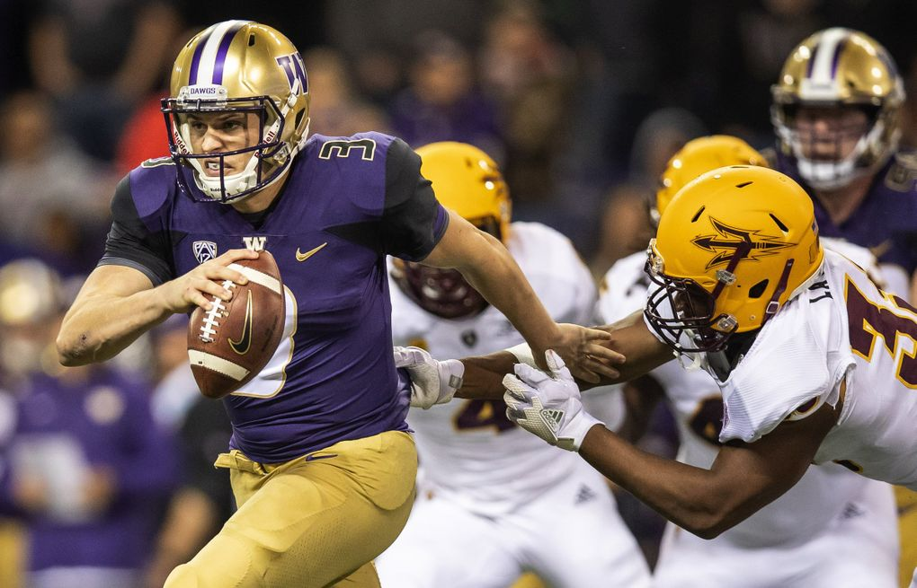 Jake Browning escapes defenders in UW's former Nike threads. (Dean Rutz / The Seattle Times)
