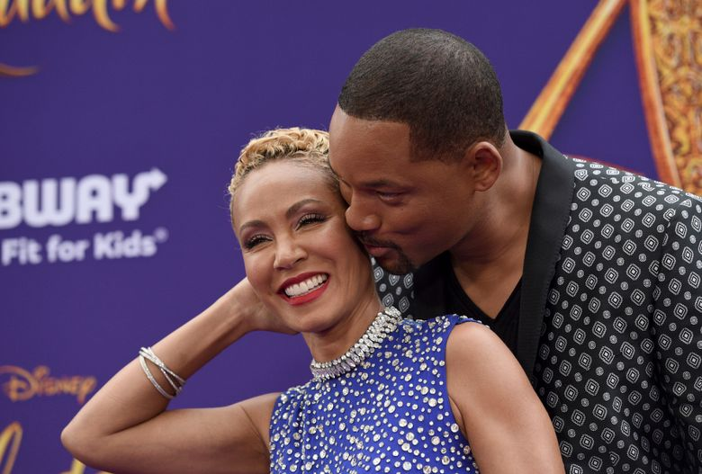 """FILE – In this May 21, 2019 file photo, Will Smith, right, kisses Jada Pinkett Smith as they arrive at the premiere of """"Aladdin"""" at the El Capitan Theatre in Los Angeles. The Hollywood power couple on Wednesday announced the launch of a new media venture. According to a statement, Westbrook Inc. will be a cross-platform holding company """"formed to execute the Smith family's global content and commerce business strategy."""" (Photo by Chris Pizzello/Invision/AP, File)"""