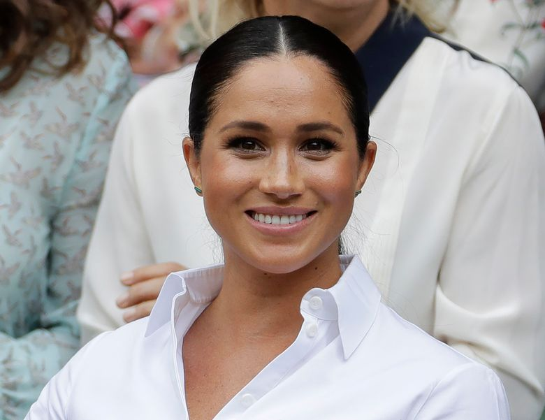 """FILE – In this July 13, 2019 file photo, Kate, Meghan, Duchess of Sussex smiles while sitting in the Royal Box on Centre Court to watch the women's singles final match between Serena Williams, of the United States, and Romania's Simona Halep on at the Wimbledon Tennis Championships in London. Meghan has guest edited the September issue of British Vogue with the theme """"Forces for Change."""" Royal officials say the issue coming out Aug. 2 features """"change-makers united by their fearlessness in breaking barriers"""" and includes a conversation between Meghan and former U.S. first lady Michelle Obama.  (AP Photo/Ben Curtis, File)"""