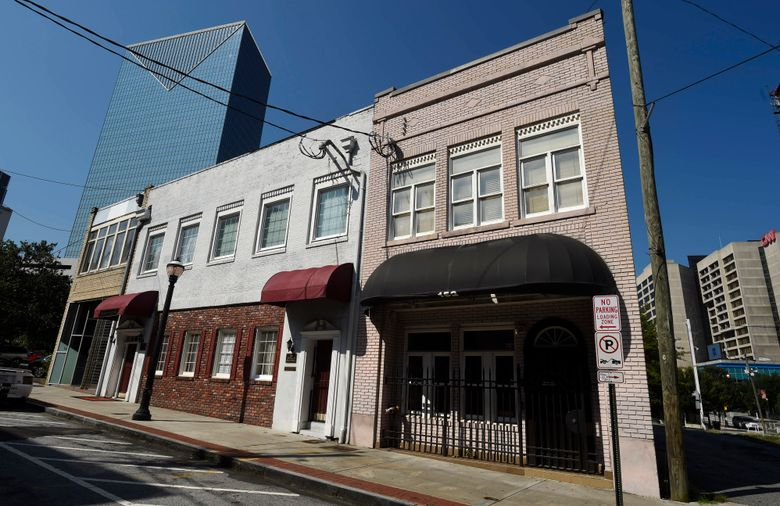"""FILE – This July 19, 2017, file photo shows a two-story brick building, right, at the northwest edge of Atlanta's old downtown. Thousands of petitioners are hoping to stop the demolition of the downtown Atlanta building where the first country hit song is believed to have been recorded. The Atlanta Journal-Constitution reports Fiddlin' John Carson likely recorded """"Little Log Cabin in the Lane"""" in the building in 1923. Last month, a Myrtle Beach-based developer planning to build a 21-story Margaritaville-themed hotel obtained a permit to tear the building down.  (AP Photo/Mike Stewart, File)"""