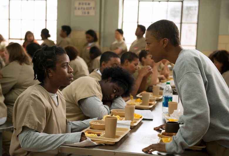 """FILE – In this file image released by Netflix, Uzo Aduba, left, and Samira Wiley appear in a scene from """"Orange is the New Black."""" The series' creative team said Thursday it has formed a fund that will support advocacy groups pressing for criminal justice reform and women re-entering society from prison, protect immigrants' rights and end mass incarceration. The fund, named in honor of show character Poussey Washington, will spread out every donation equally to eight already-existing nonprofit groups. The announcement comes on the eve of the Friday premiere of the series' seventh and final season. (Jojo Whilden/Netflix via AP, File)"""