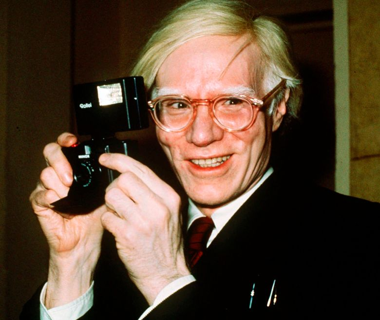"""FILE – In this 1976 file photo, pop artist Andy Warhol smiles in New York. Warhol transcended a photographer's copyright by transforming a picture of a vulnerable and uncomfortable Prince into an artwork that made the singer an """"iconic, larger-than-life figure,"""" a judge ruled Monday, July 1, 2019. (AP Photo/Richard Drew, File)"""