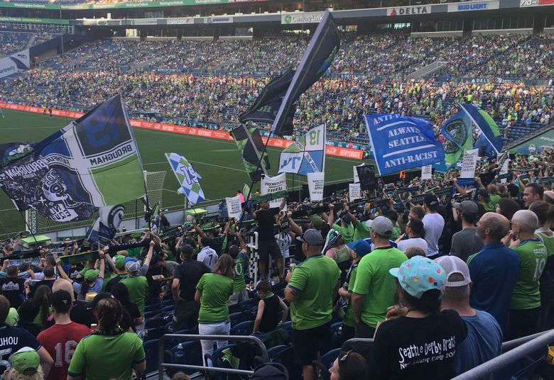 """Sounders fans in the Brougham End of CenturyLink Field wave """"Anti-fascist/Anti-Racist/Always Seattle"""" flags prior to the team's match against Sporting KC on Sunday. The supporters group was issued a warning from MLS for waving an Iron Front flag during a game against Portland on July 21.  (Jayda Evans / The Seattle Times)"""