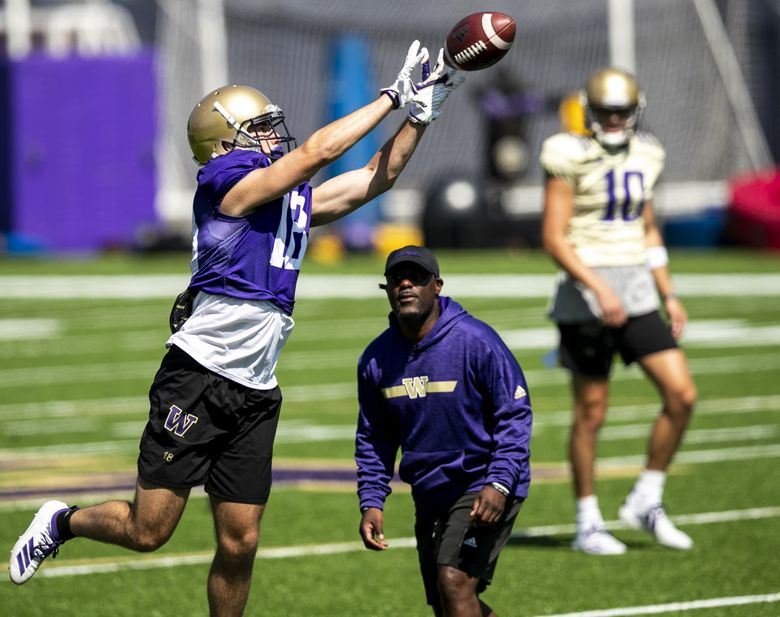 Huskies wide receiver Austin Osborne jumps up for a catch in front of Junior Adams, wide receivers coach, as the University of Washington holds day five of football training camp at Husky Stadium Tuesday August 6, 2019. (Bettina Hansen / The Seattle Times)