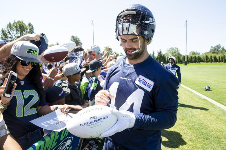 Seahawks fullback Nick Bellore signs autographs for fans after Seahawks training camp Aug. 1 at the Virginia Mason Athletic Center in Renton. (Bettina Hansen / The Seattle Times)