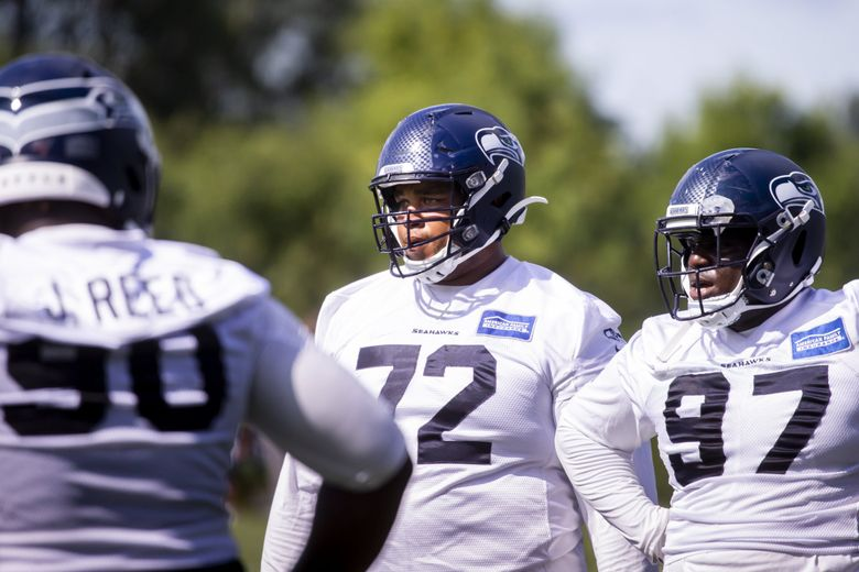 Seahawks defensive tackle Al Woods works out with his unit at training camp at the Virginia Mason Athletic Center in Renton on Thursday. Jarran Reed is to the left and Poona Ford is to the right. (Bettina Hansen / The Seattle Times)