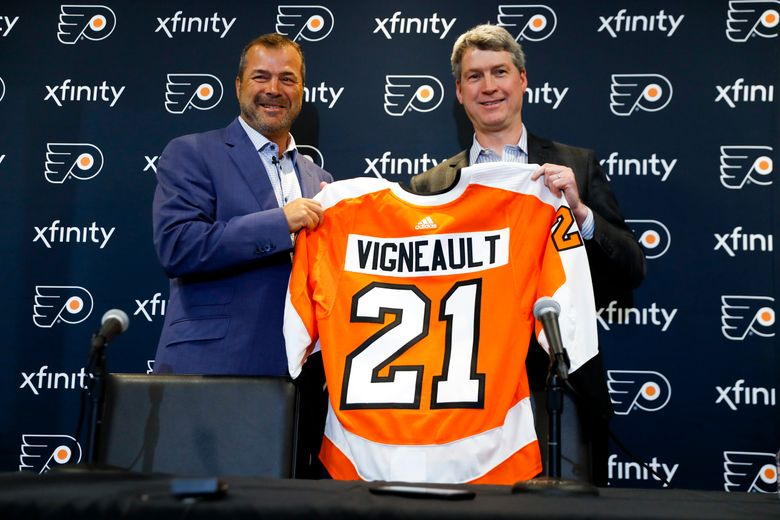 """FILE – In this April 18, 2019, file photo, Alain Vigneault, left, newly hired Philadelphia Flyers head coach, and general manager Chuck Fletcher pose for a photograph after an introductory press conference at the Flyer's practice facility in Voorhees, N.J. When NHL officials approached the Philadelphia Flyers about appearing on their latest behind-the-scenes show, they faced almost no resistance. """"There weren't many reservations,"""" general manager Chuck Fletcher said. """"There really aren't any negatives as far as I'm concerned."""" The Flyers will be featured on NHL Network's second season of """"Behind the Glass"""" that gives a peek behind the curtain to training camp, exhibition games and the regular-season opener in Europe. (AP Photo/Matt Slocum, File)"""