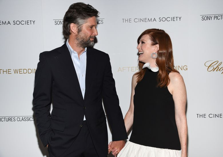"""FILE – In this Tuesday, Aug. 6, 2019 file photo, director Bart Freundlich, left, and wife, actor Julianne Moore, attend a special screening of """"After the Wedding"""" in New York. The film, written and directed by Freundlich, is a remake of director Susanne Bier's hit Dutch movie of the same name. (Photo by Evan Agostini/Invision/AP)"""