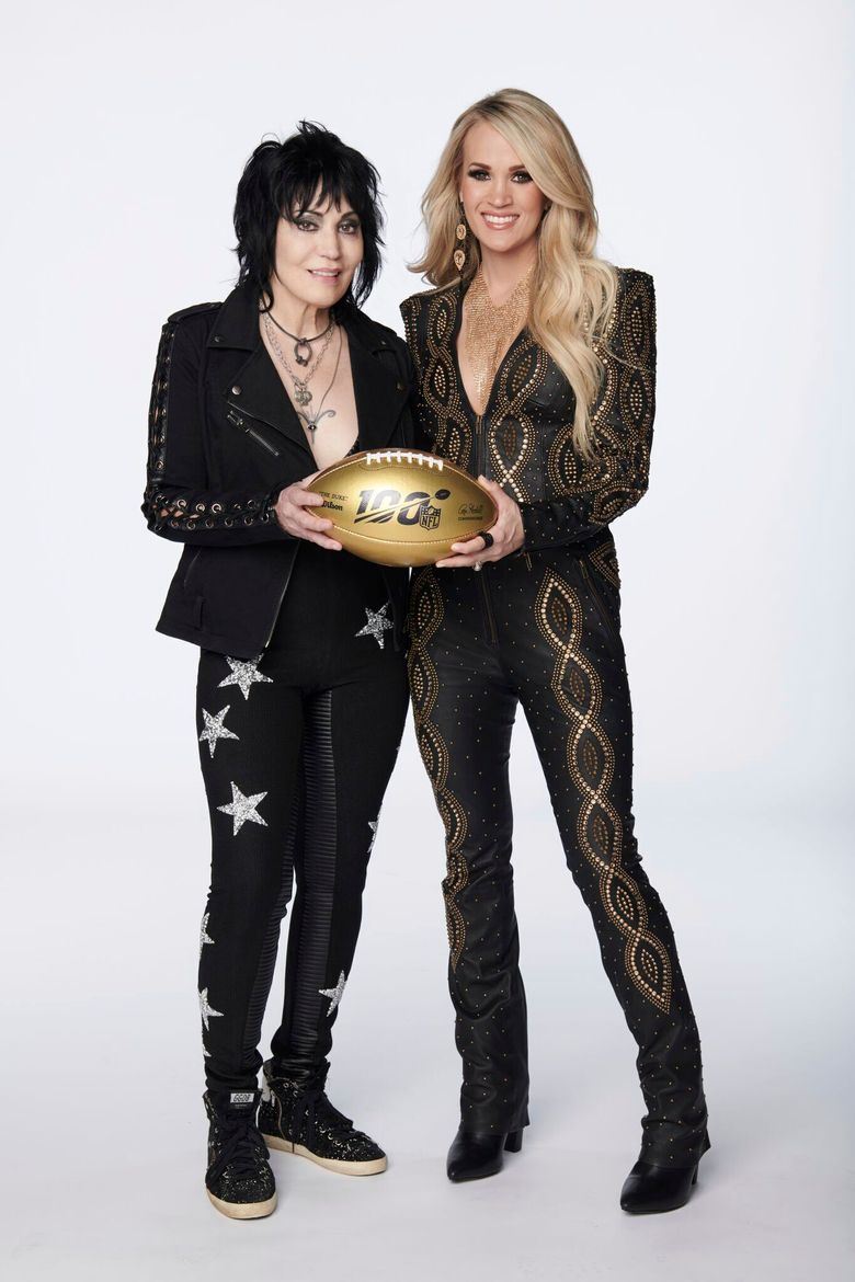 In this photo provided by NBC Sports, Joan Jett, left, and Carrie Underwood pose with a 100th anniversary NFL football. NBC's Sunday Night Football open will return to the original Waiting All Day for Sunday Night song, but this time Carrie Underwood will be joined by Rock & Roll Hall of Fame inductee Joan Jett. Her band, the Blackhearts, also perform in the open, which features NFL stars. (Virginia Sherwood/NBC Sports via AP)