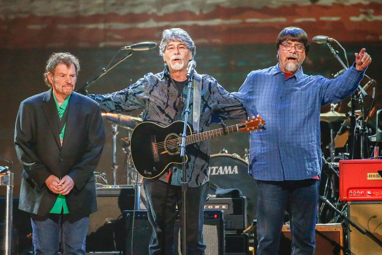 FILE – This April 6, 2017 file photo shows Jeff Cook, from left, Randy Owen and Teddy Gentry, from the southern rock band Alabama, performing at the Bridgestone Arena in Nashville, Tenn. The band says it is postponing the remainder of its 50th anniversary tour as lead singer Owen battles health complications. The band announced Wednesday, Aug. 21, that the 69-year-old singer is suffering from migraines and vertigo, and doctors say he needs more time to recover. (Photo by Al Wagner/Invision/AP, File)