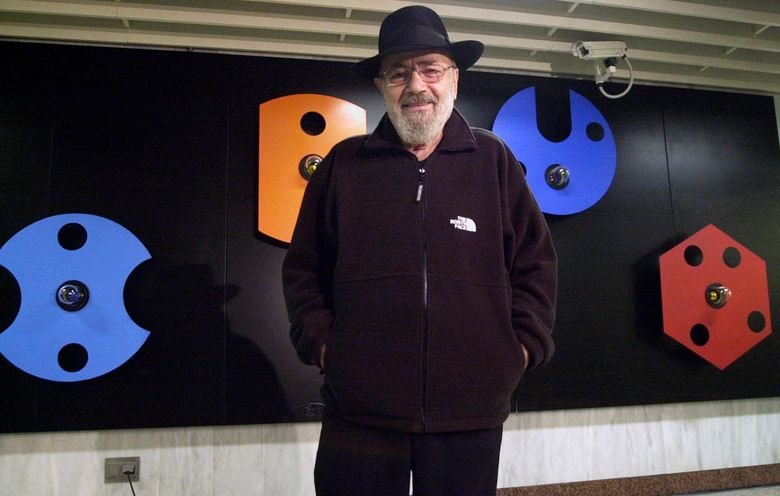 FILE – In this Jan. 29, 2001 file photo Greek sculptor Takis poses in front of his artwork at a metro station in Athens. Greek sculptor Takis, known for artworks that made use of technology, motion and light and were displayed in art galleries and museums around the world, has died, his foundation said Friday, Aug. 2019. He was 93. (Stratos Chavalezis/Eurokinissi via AP, File)