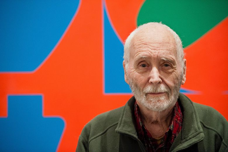 FILE – In this Sept. 24, 2013, file photo, artist Robert Indiana, known for his LOVE artwork, poses in front of that painting at New York's Whitney Museum of American Art. Court documents indicate pop artist Robert Indiana had $13 million in the bank even as his house sank into disrepair before his death. Documents filed Wednesday, August 14, 2019 by Indiana's estate alleged his aide, Jamie Thomas, was not a selfless caregiver. (AP Photo/Lauren Casselberry, File)