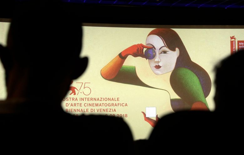 FILE – In this Wednesday, July 25, 2018, file photo, journalists are silhouetted against the logo presenting the 75th edition of the festival, during its presentation in Rome. It may be the oldest film festival in the world but at 76, the Venice International Film Festival is more relevant, and divisive, than ever. Kicking off Wednesday, Aug. 28, 2019,  on the sleepy beach town of Lido, this year's festival has already become a hotbed for discussion about the Oscar hopefuls launching there, its embrace of controversial filmmakers like Roman Polanski and Nate Parker in the #MeToo era and its lack of female directors. (AP Photo/Gregorio Borgia, File)