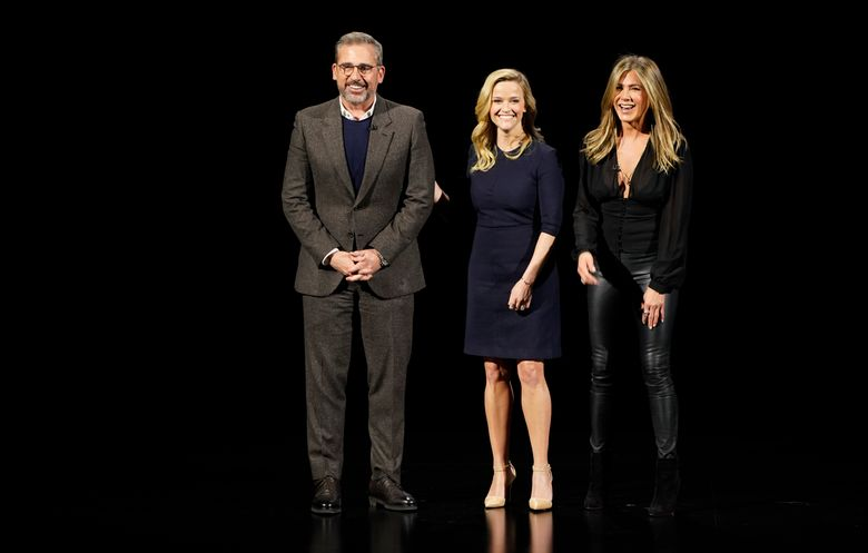 """FILE – In this March 25, 2019, file photo, from left, Steve Carell, Reese Witherspoon and Jennifer Aniston speak at the Steve Jobs Theater in Cupertino, Calif. Apple is offering a first look at its web television series """"The Morning Show."""" It posted a teaser of the show, which stars Reese Witherspoon, Jennifer Aniston and Steve Carell. The drama seeks to give a behind-the-scenes view of early-morning TV. """"The Morning Show"""" will debut this fall on AppleTV+. (AP Photo/Tony Avelar)"""