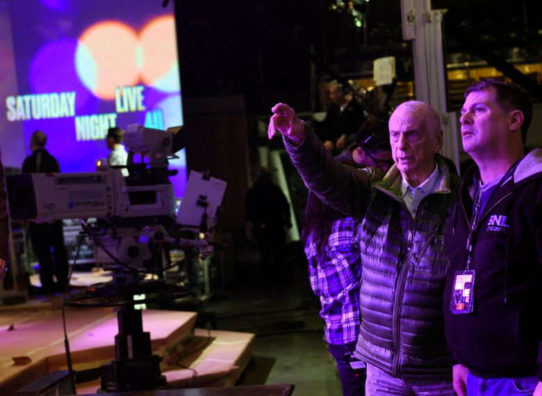"""This  Feb. 3, 2015 photo released by NBC shows lighting designer Phil Hymes, second right, with lighting director Geoff Amoral on the set of """"Saturday Night Live,"""" in New York. NBC says Emmy-winning lighting director Hymes has died. He was 96, and worked on """"Saturday Night Live"""" until 2018. NBC said that Hymes died of complications from cancer at a New York City hospital Monday, Aug. 29, 2019. (Dana Edelson/NBC via AP)"""