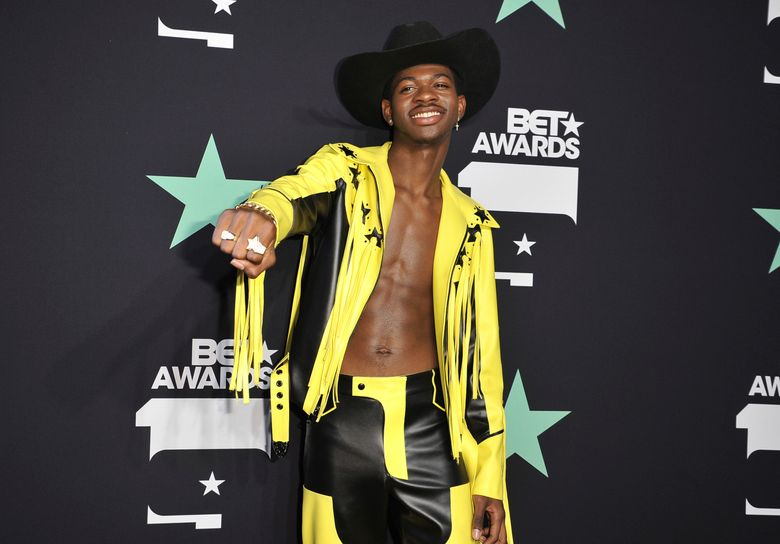 """FILE – In a Sunday, June 23, 2019 file photo, Lil Nas X poses in the press room at the BET Awards, at the Microsoft Theater in Los Angeles. Lil Nas X has set two new records on Billboard's Hot R&B/Hip-Hop songs and Hot rap songs charts. """"Old Town Road,"""" which is spending its 19th week at No. 1, surpasses the record set by Drake's """"One Dance"""" on the R&B/Hip-Hop songs chart.(Photo by Richard Shotwell/Invision/AP, File)"""