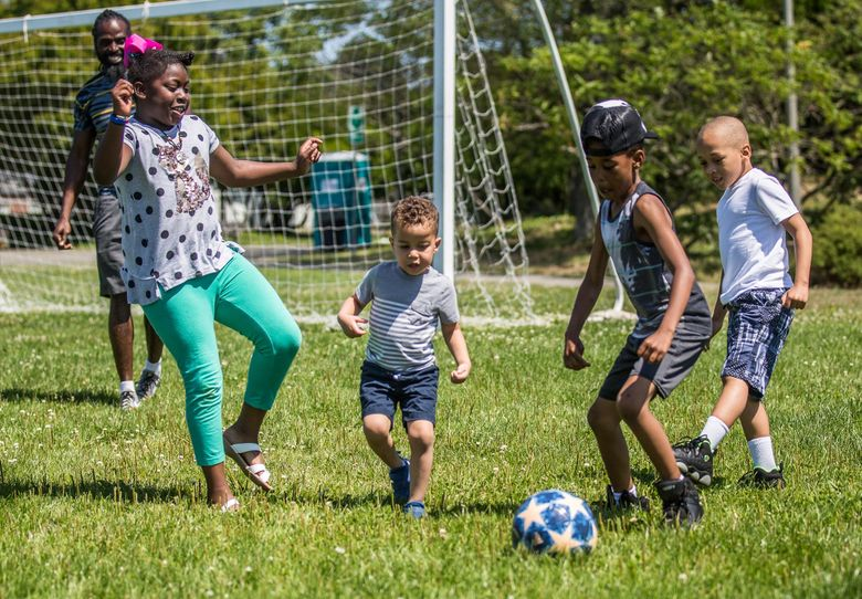 Kids play soccer behind the booths at the Caribbean Sea Fest in Jimi Hendrix Park on a Sunday in July 2019. (Rebekah Welch / The Seattle Times)