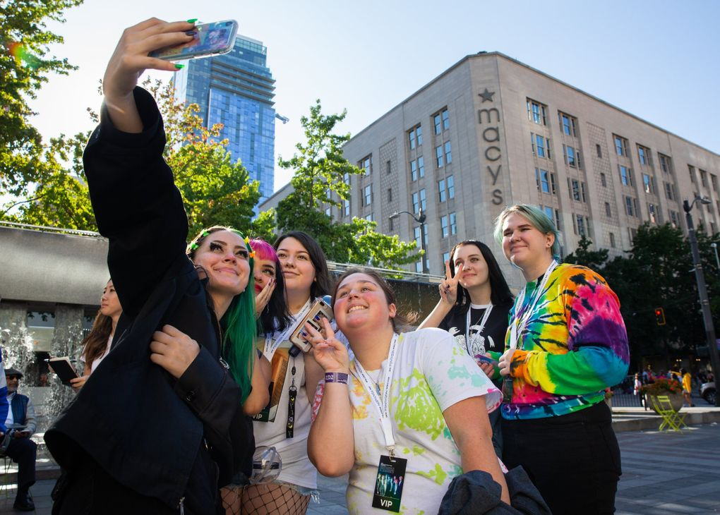 Pentagon fans take a photo together in Westlake Park during the fan-group meetup before Tuesday's concert at Moore Theatre in Seattle. (Andy Bao / The Seattle Times)