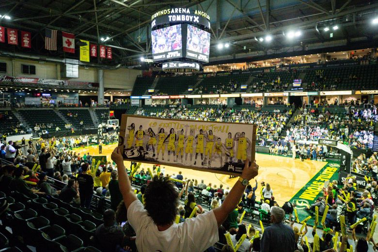 """Storms fan Debbie Gwaltney waves a sign during the game one of the WNBA playoffs between the Seattle Storm and the Minnesota Lynx at the Angel of the Winds Arena in Everett, WA, on Sept. 11, 2019. """"I've been coming to the games since the early 2000's"""" said Gwaltney. (Andy Bao / The Seattle Times)"""