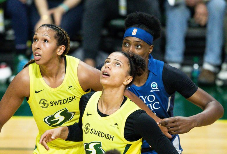 The Storm's Mercedes Russell (2), left, Alysha Clark (32), center, and the Lynx's Sylvia Fowles (34) watch a free throw during the game one of the WNBA playoffs between the Seattle Storm and the Minnesota Lynx at the Angel of the Winds Arena in Everett, WA, on Sept. 11, 2019. (Andy Bao / The Seattle Times)
