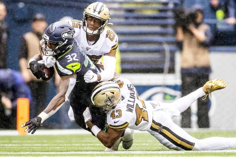 Saints cornerback Eli Apple punches the ball out of the hands of Seahawks running back Chris Carson, forcing him to fumble at the end of a 23-yard run, and it's picked up by Saints strong safety Vonn Bell and run back for a 33-yard touchdown in the second quarter as the Seattle Seahawks take on the New Orleans Saints at CenturyLink Field in Seattle Sunday September 22, 2019. (Dean Rutz / The Seattle Times)