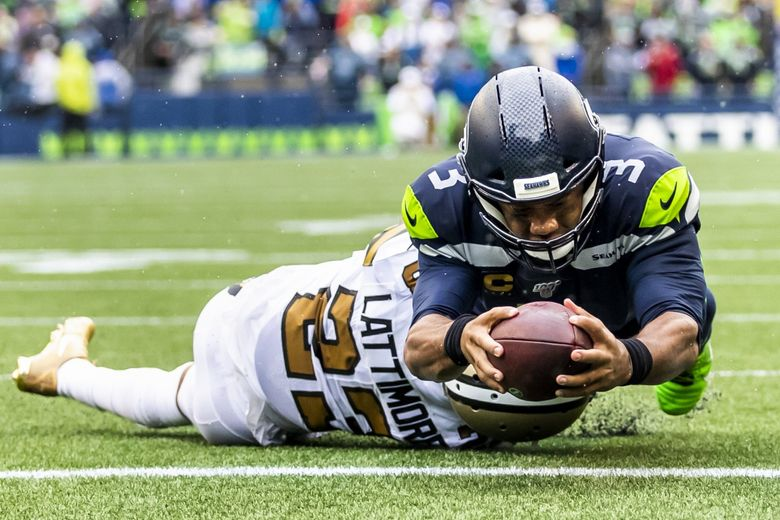 Seahawks quarterback Russell Wilson scores a 2-yard rushing touchdown over Saints cornerback Marshon Lattimore in the fourth quarter Sunday at CenturyLink Field. (Dean Rutz / The Seattle Times)