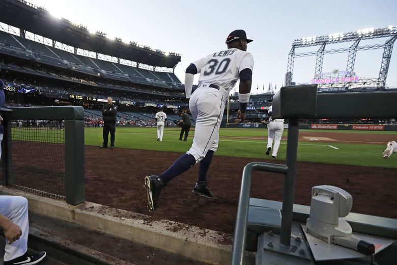 Seattle Mariners right fielder Kyle Lewis runs out of the dugout for his debut in the majors, against the Cincinnati Reds on Tuesday. (Ted S. Warren / AP)