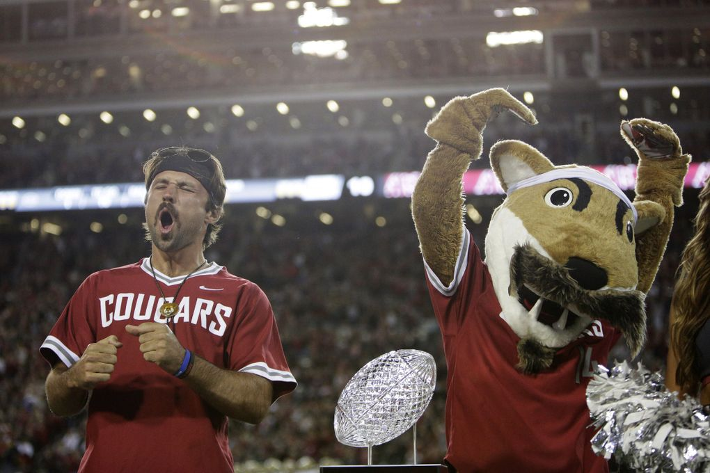 Gardner Minshew, left, and Cougars mascot Butch react as Minshew is recognized on the field during a game in 2019. (Young Kwak / The Associated Press)