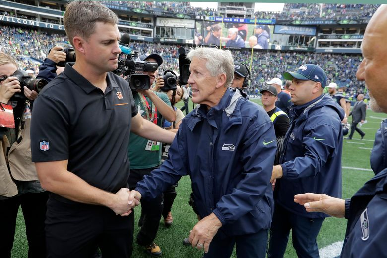 Seattle Seahawks head coach Pete Carroll, center, shakes hands with Cincinnati Bengals head coach Zac Taylor, left, after an NFL football game, Sunday, Sept. 8, 2019, in Seattle. (AP Photo/John Froschauer)