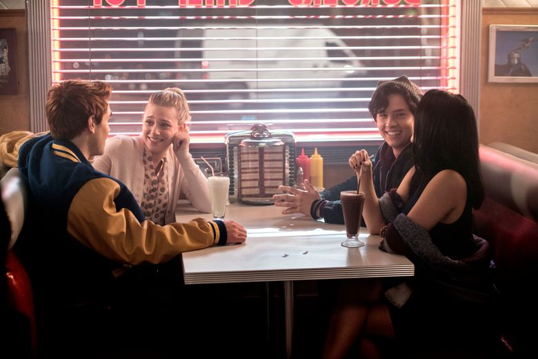 """This image released by The CW shows, from left, KJ Apa as Archie Andrews, Lili Reinhart as Betty Cooper, Cole Sprouse as Jughead Jones, and Camila Mendes as Veronica Lodge, in a scene from """"Riverdale."""" The cast and creators of """"Riverdale"""" will receive an award from a gay rights education group for the show's portrayal of LGBTQ relationships in a high school setting.  (Diyah Pera/The CW via AP)"""
