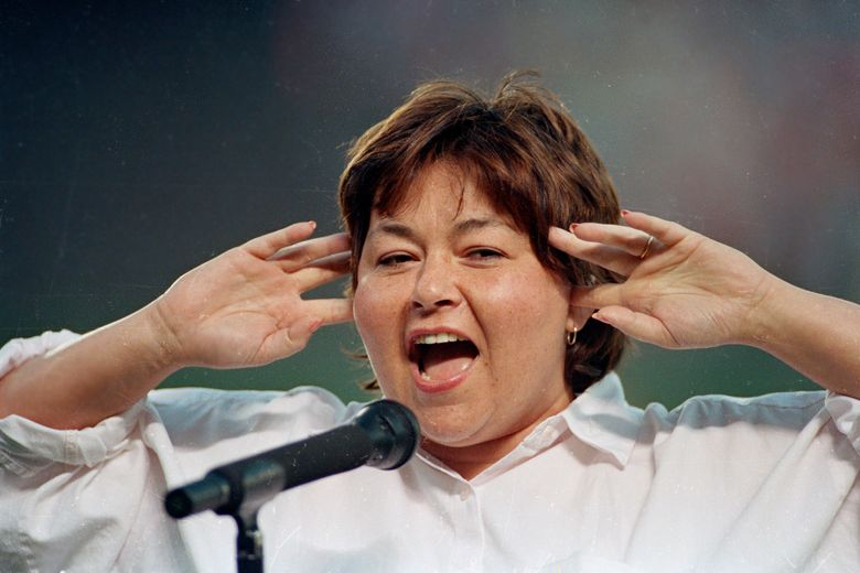 FILE – In this July 25, 1990, file photo, comedienne Roseanne Barr holds her fingers in her ears as she screams the National Anthem between games of the San Diego Padres and the Cincinnati Reds doubleheader in San Diego, Calif. A Delaware school district played a parody version of the national anthem before a volleyball match, surprising spectators with Barr's screeching 1990s rendition. The News Journal of Wilmington reports the Seaford School District apologized Wednesday, Sept. 25, 2019, for the shock at its Tuesday game with Milford High. Superintendent David Perrington says pre-game proceedings will be improved. Officials didn't say how Barr's version, performed before a San Diego Padres game, came to be used. (AP Photo/Joan Fahrenthold, File)