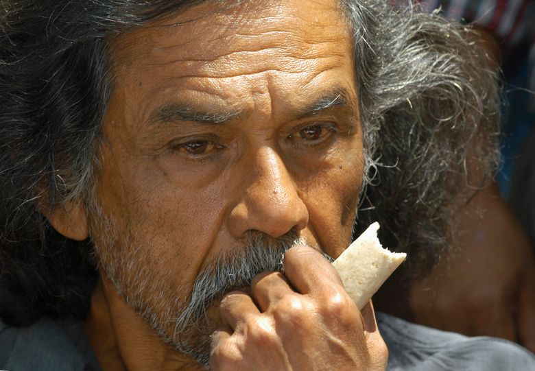 FILE – In this March 11, 2004 file photo, Francisco Toledo, one of Mexico's most prominent painters, eats a corn tortilla in the city center of Oaxaca, Mexico, to protest the presence of genetically modified corn in the Mexican wild. The family of Toledo has announced on Thursday, September 5, 2019, the he has died. (AP Photo/Marco Ugarte, File)