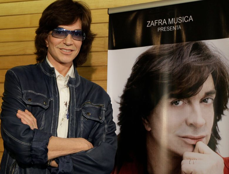 FILE – In this Nov. 4, 2009, file photo, Spanish singer Camilo Sesto poses next to a poster depicting himself during a news conference in Mexico City. Spanish singer and songwriter Camilo Sesto, a popular star in the 1970s and 1980s, has died of heart failure early on Sunday Sept. 8, 2019. He was 72. Sesto, whose real name was Camilo Blanes Cortes, sold more than 100 million records worldwide over his 40-year career. (AP Photo/Gregory Bull, file)