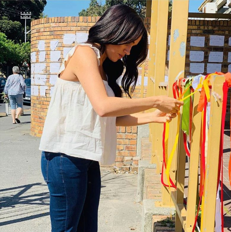 """In this undated handout photo taken from the Sussex Royal instagram account, Britain's Meghan, the Duchess of Sussex visits the memorial to a murdered South African student as a """"personal gesture"""" after """"closely following the tragic story"""". In a quiet visit, Meghan tied a ribbon to the memorial at the post office where university student Uyinene Mrwetyana was attacked. A post on the royals' Instagram account calls the death """"a critical point in the future of women's rights in South Africa,"""" where more than 100 rapes are reported every day. (Sussex Royal via AP)"""