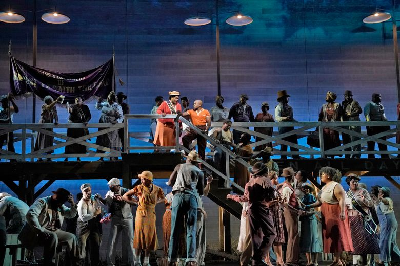 """This image released by the Metropolitan Opera shows Latonia Moore as Serena, center left on stairs, and Frederick Ballentine as Sportin' Life in a scene from the Gershwins' """"Porgy and Bess."""" (Ken Howard/Met Opera via AP)"""