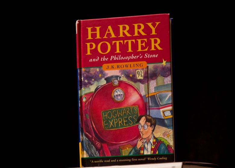 """FILE – This May 20, 2013, file photo shows a first edition copy of the first Harry Potter book """"Harry Potter and the Philosopher's Stone"""" during a photocall organized for the media at the Sotheby's auction house's premises in London. A Catholic school in Tennessee has removed the Harry Potter books from its library after the school's priest decided they could cause a reader to conjure evil spirits. (AP Photo/Matt Dunham, File)"""