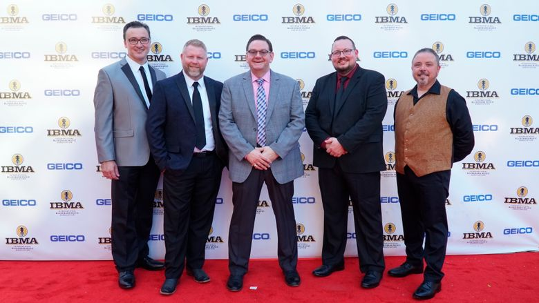 This photo provided by IBMA shows the bluegrass band Joe Mullins and the Radio Ramblers, from left, Jason Barie, Mike Terry, Joe Mullins, Adam McIntosh, Randy Barnes.  The band won entertainer of the year and collaborative recording of the year at the 30th annual International Bluegrass Music Awards, Thursday, Sept. 26, 2019 in Raleigh, N.C. (Dan Schram/IBMA via AP) .