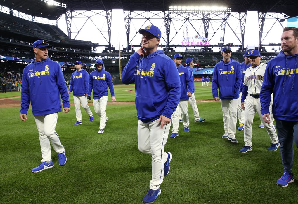 The season is over, as Mariners manager Scott Servais, center, and pitching coach Paul Davis, left, leave the field after defeating Oakland during the M's season finale, Sunday, Sept. 29, 2019 at T-Mobile Park in Seattle. (Ken Lambert / The Seattle Times)