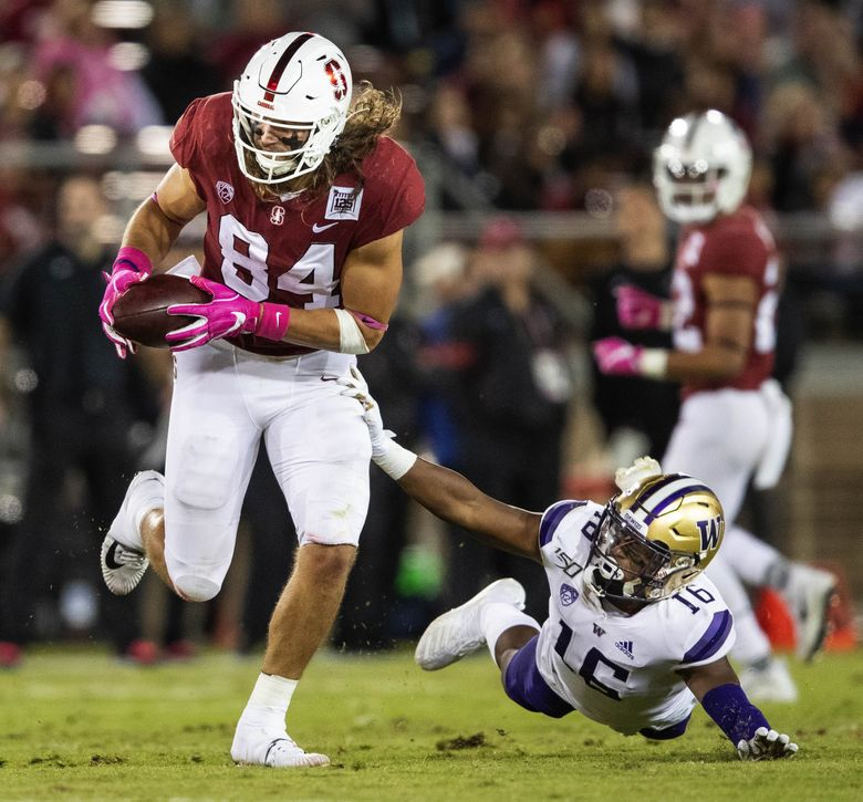 Stanford's Colby Parkinson bobbles the pass but manages to retain control, and blows past Washington's Cameron Williams. (Dean Rutz / The Seattle Times)