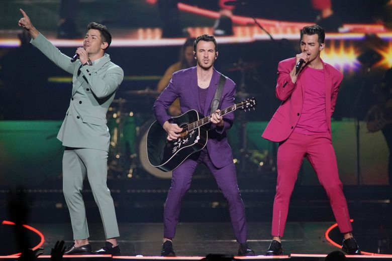 """The Jonas Brothers — from left, Nick, Kevin and Joe Jonas — perform during their """"Happiness Begins Tour"""" on Sept. 19 in Chicago. (Rob Grabowski / Invision / AP)"""