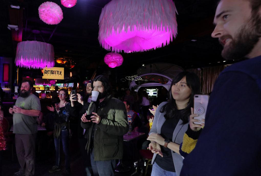 Audience members keep track of the artists' progress during each timed round at Art Battle Seattle. (Alan Berner / Seattle Times)