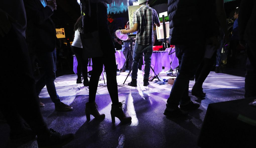 With the feeling of a nightclub, Art Battle Seattle begins a 20-minute round of competition. Each canvas is the same size and acrylic paint is provided.  Audience members walk in a counterclockwise circle around the artists as they work. (Alan Berner / Seattle Times)