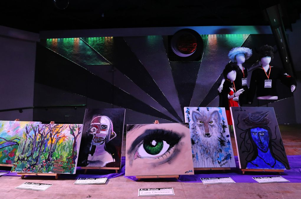 Completed paintings from the first round of competition during September's Art Battle Seattle are placed on stage at Eden Seattle in Sodo. (Alan Berner / Seattle Times)