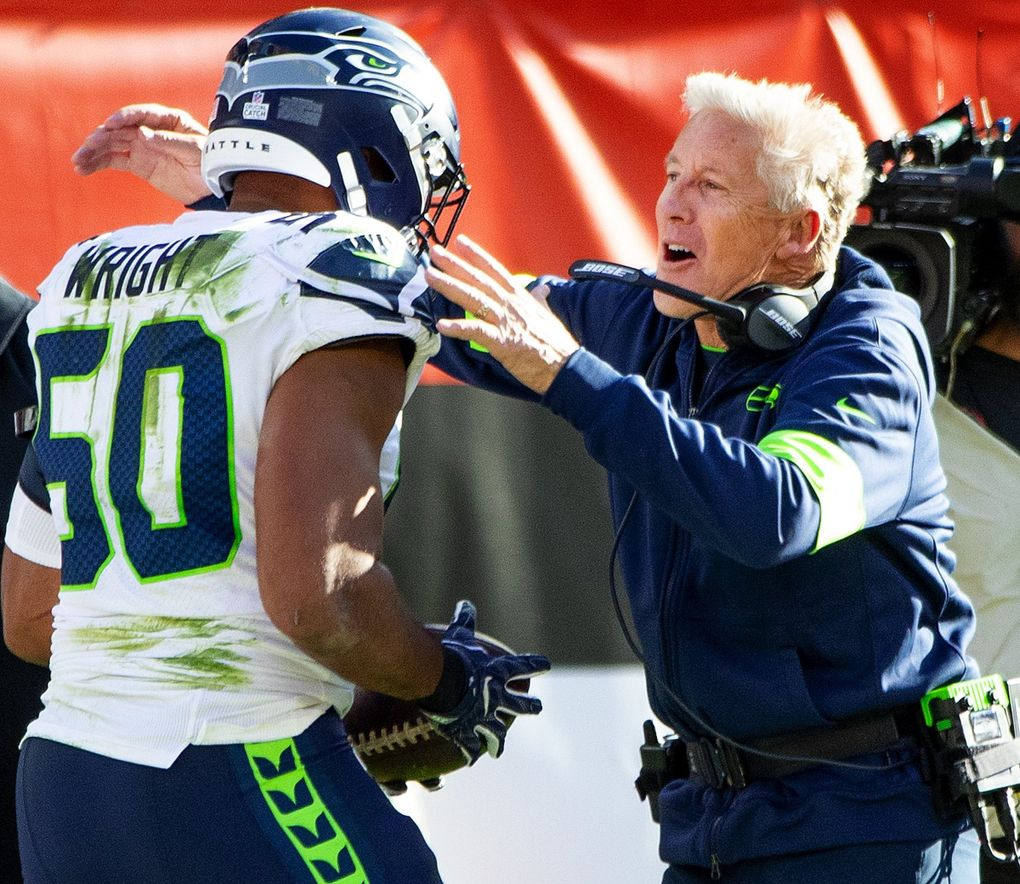Seahawks head coach Pete Carroll embraces outside linebacker K.J. Wright after Wright intercepted Browns quarterback Baker Mayfield, sealing the Seattle victory Sunday in Cleveland. (Mike Siegel / The Seattle Times)