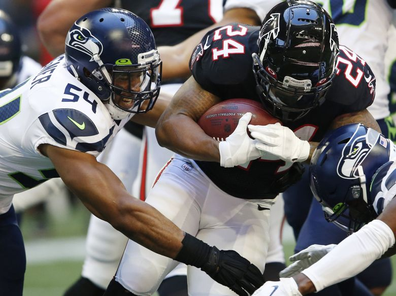 Bobby Wagner tackles Falcons running back Devonta Freeman on Sunday in Atlanta. (John Bazemore / The Associated Press)